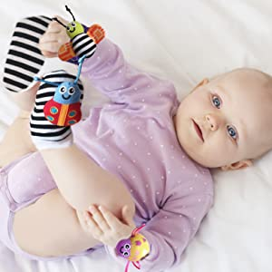 Baby girl finding her foot. She is wearing the wrist rattles and rattle socks