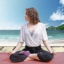 Woman doing seated yoga pose in purple Pakari socks on boardwalk in front of sea.