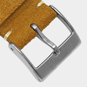 closeup of suede leather watch strap showing brushed silver tang buckle