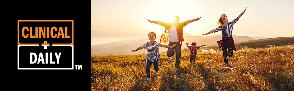 parents and children running in a field with sunshine behind them