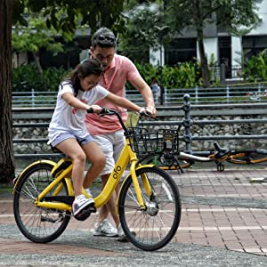 Father helping a daughter ride her bicycle in a park