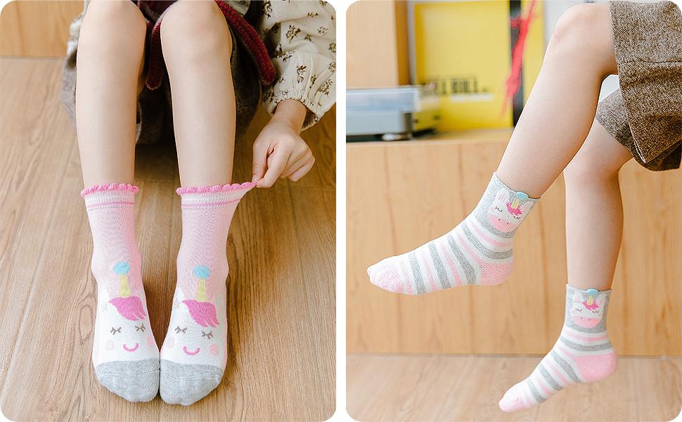 Una niña viste el calcetines cortos elásticas, en pack de 5 pares en distintos colores y rayas.