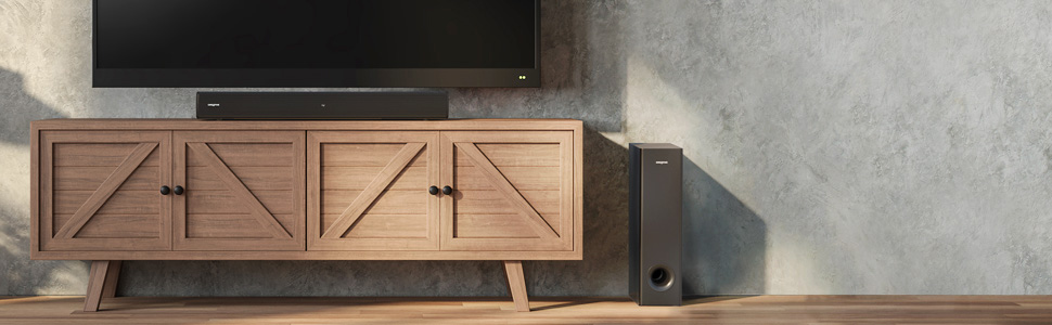 Soundbar resting on wooden TV console below TV, with subwoofer on the floor on the right