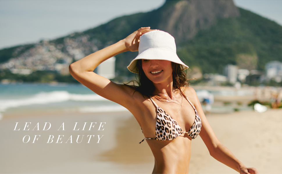 lady in leopard print bikini on beach with white hat. Text reads Lead a life of beauty