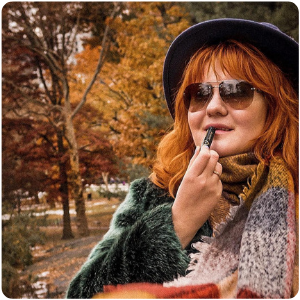A woman in a park putting on her Aubio Hydrating Lip Balm during the Fall season with leaves falling