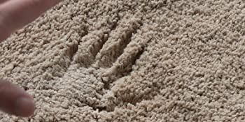 Plush shaggy bath mat in beige with hand print to show how thick it is.
