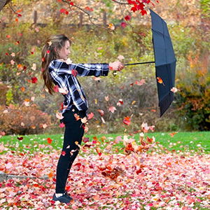 Woman holding umbrella while the wind blow. Umbrella is still holding it's shape and is very sturdy