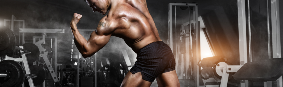 Body builder, male, in a dark, fully equipped home gym with fog, leaning forward, flexing arm
