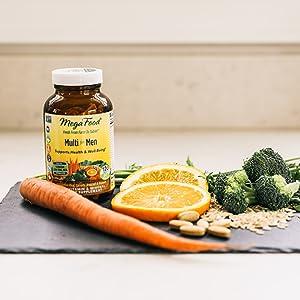 Carrot, orange and broccoli on a cutting board
