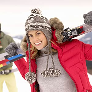 a smiling skier atop a snowy mountain wearing a red jacket after using Aubio Cold Sore Treatment Gel