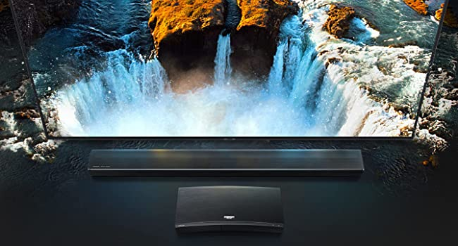 QLED TV with a waterfall on screen, Soundbar below
