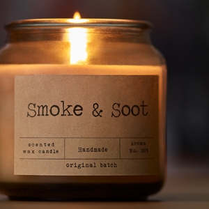 lit candle with label that says Smoke & Soot