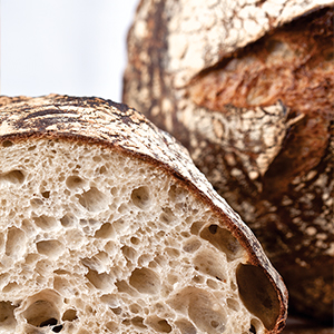 Photograph of inside of baked bread loaf with crispy crust and soft crumb