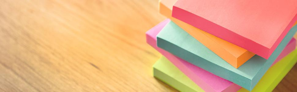 Stack of Post-it Notes on a table.
