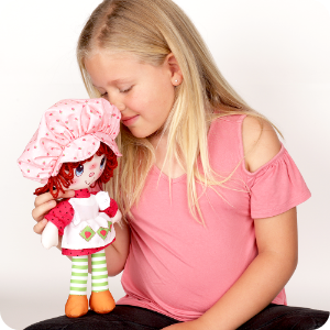 Lifestyle image of girl smelling doll