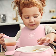 Girl wearing the pink bib with the spoon plate and cup in front of her