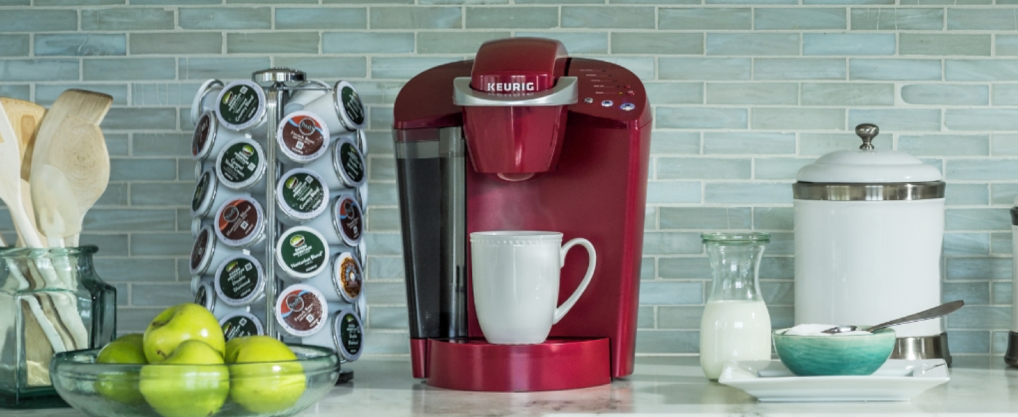 red keurig k55 on a counter surrounded by k-cups and kitchen things