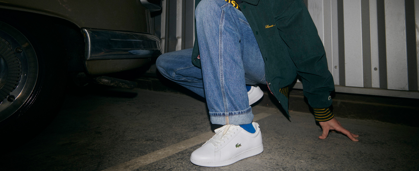 Le scarpe da ginnastica Carnaby Evo indossate con una tuta Lacoste bianca e nera