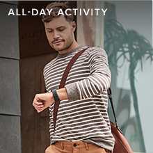 Man in strioed shirt looking at watch while walking