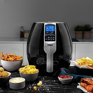 Friteuse à air chaud Princess XL sur comptoir de cuisine entourée de frites et de coupelles de sauce