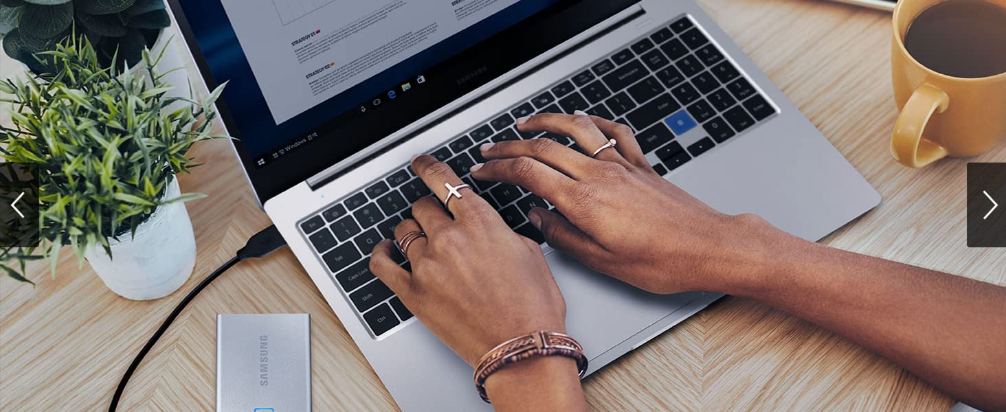 Woman using her laptop while it is connected to Samsung Portable SSD T7 Touch