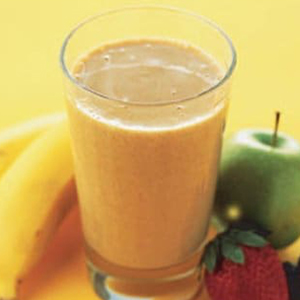 Glass of Nutri-Grain power shake with a banana, apple and strawberry in the background