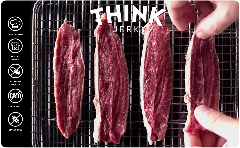 Freshly cut beef jerky Strips being hand laid on the grill by Think Jerky