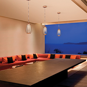 Large outdoor living space with washed copper outdoor pendant lights over table with ocean view.