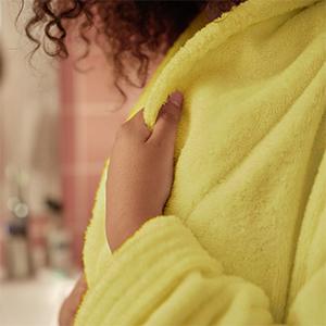Vrouw in haar badjas ruikt en voelt aan de zachte en felgekleurde gele stof van de ochtendjas