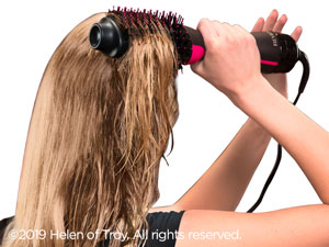 A woman using Revlon Brush Hair Dryer