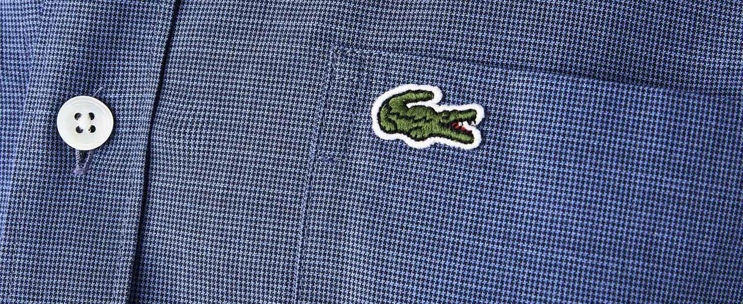 Detalle de botón blanco de imitación de cuerno y cocodrilo verde bordado en el bolsillo