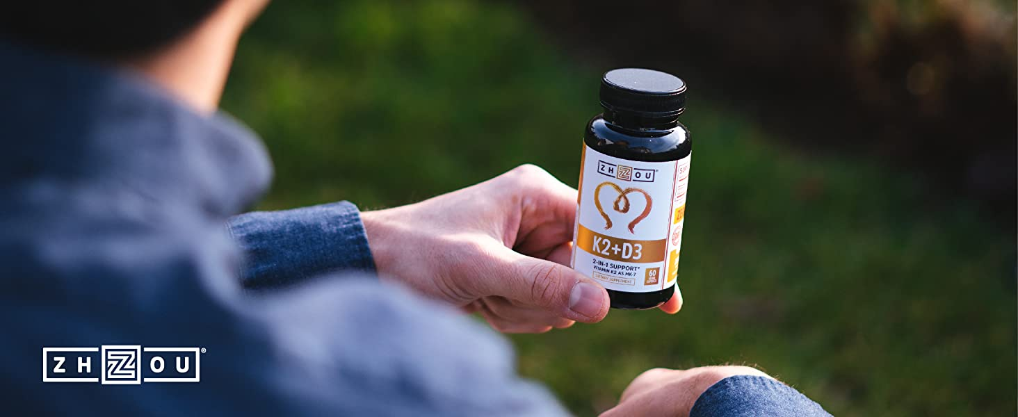 Man holding his bottle of Vitamin K2 + D3 by Zhou Nutrition