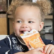 toddler eating happy tot organic food pouch