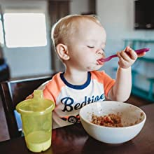 Kid eating with plastic spoon