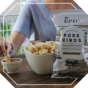 Woman eating a bowl of EPIC gluten free pork rinds snacks with dipping salsa