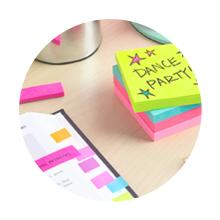 A stack of Post-it Notes on a desk. Next to it is an open notebook with several Post-it Flags markin