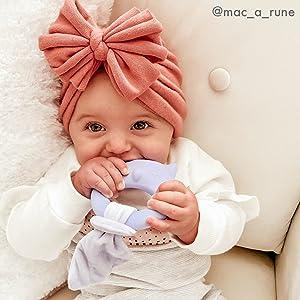 Baby girl in peach head wrap chews on owl shaped teether.