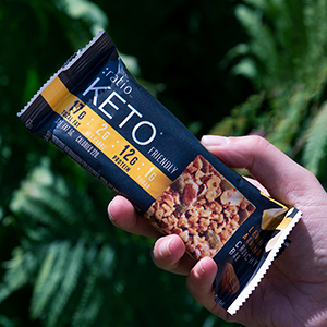 Hand holding an unwrapped :ratio crunchy snack bar