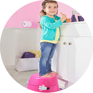 Little girl standing on step stool to reach the sink
