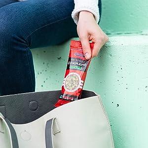 A model's hand placing an edamame packet into a handbag.