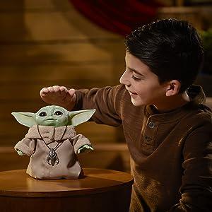 Boneco baby Yoda com uma criança ao lado