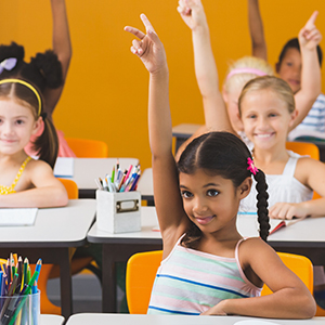 A girl raising her hand in a classroom for participation