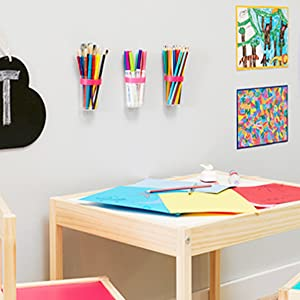 colored pencils, markers and paint brushes in small clear caddies above kids art table