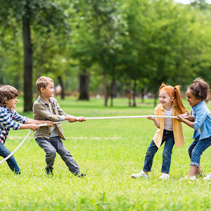young children playing tug-of-war outside at a park