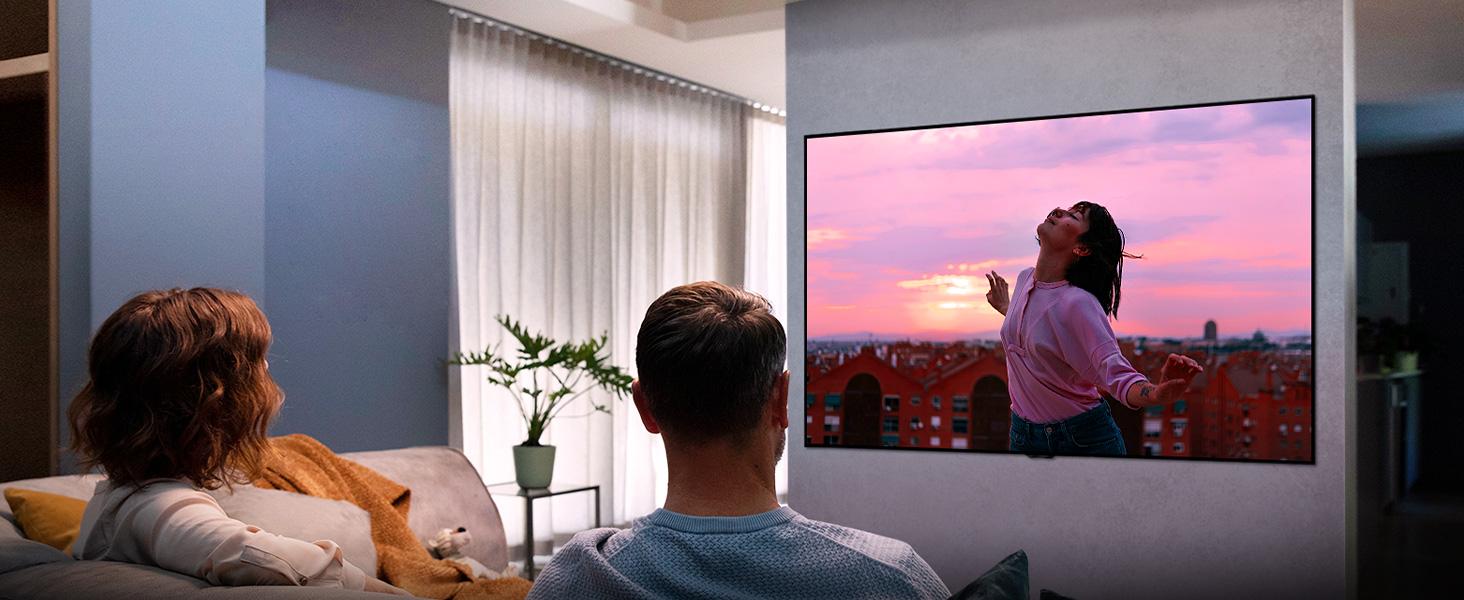 Zwei personen schauen in einem wohnzimmer einen film im filmmaker mode auf einem lg nano-cell tv