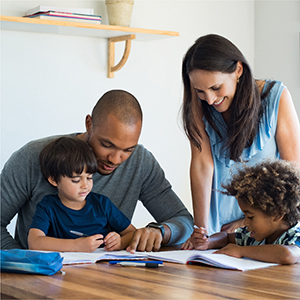 parents helping their two children with school work