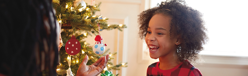 Smiling girl looking at Hallmark Keepsake Christmas ornaments hanging on a tree during the holidays