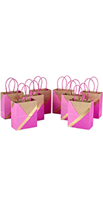 Small rose and gold gift bags with brown kraft paper accents and pink handles for baby showers