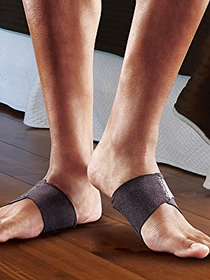 male feet wearing FUTURO arch support on wood floor