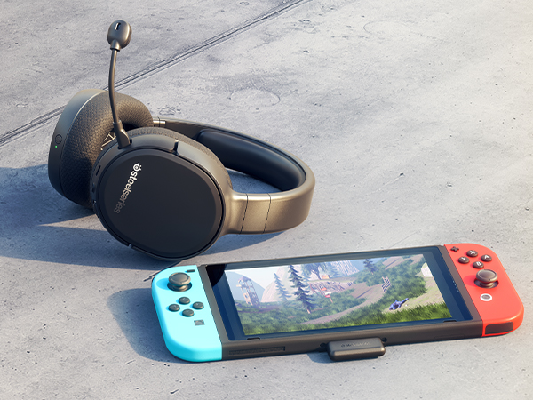 - Arctis 1 Wireless laying outdoors on a sidewalk next to a Nintendo Switch